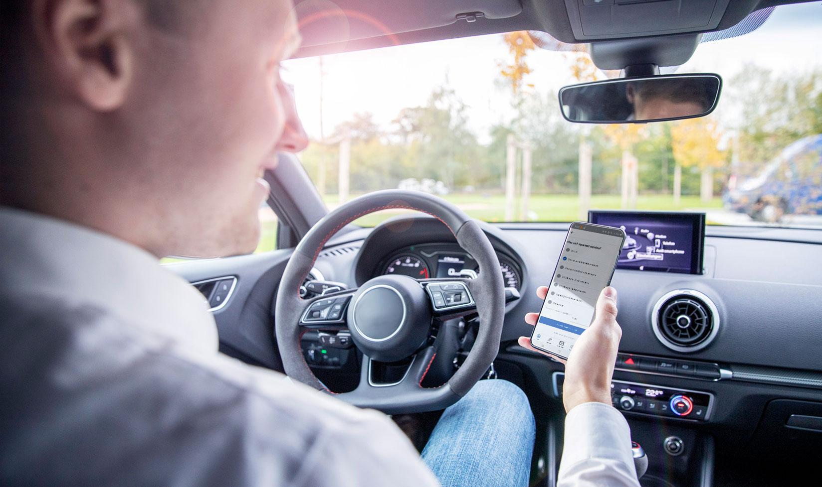 Mann im Auto Handy in der Hand