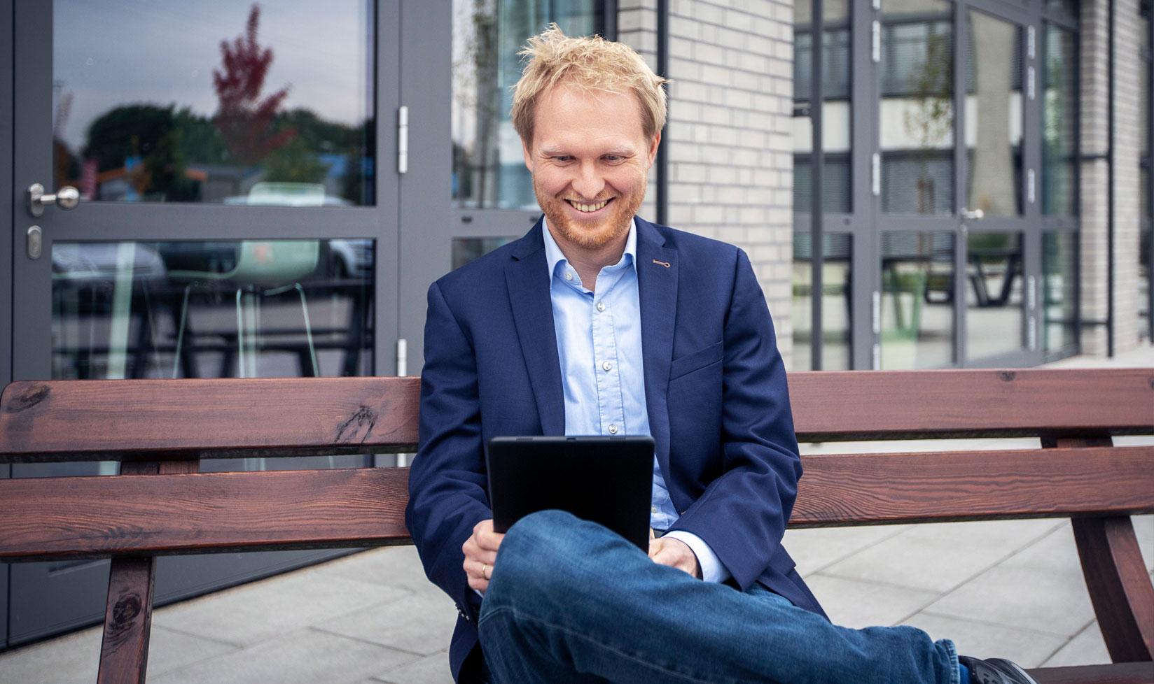 Mann sitzt auf einer Bank mit einem Tablet